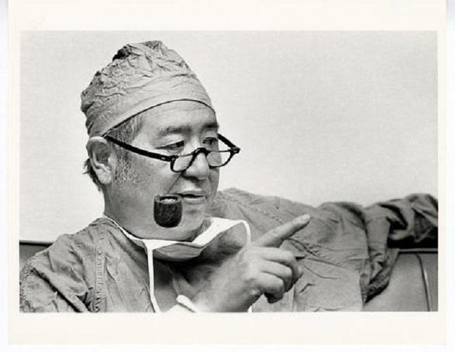 Joseph H. Ogura wearing surgical scrubs and smoking a pipe.