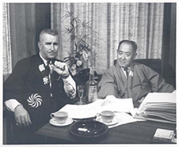 Unidentified man and Joseph H. Ogura drinking whiskey together.
