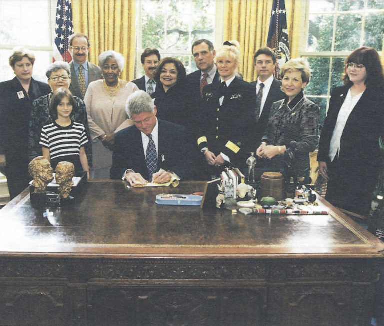 """President Bill Clinton signs the NCCS Ribbon of Hope TM and calls it """"a symbol of the progress we have made and the progress still to come."""" Survivorship leaders present include (far right) NCCS President Betsy Clark and NCCS director Ellen Stovall (next to Clark). Also on hand (l-r): Jane Reese-Coulbourne, executive vice president, National Breast Cancer Coalition; cancer survivor Olda Mondragon; cancer survivor Erin Schraibman; Harold Varmus, MD, director, National Cancer Institute; Dorothy Bankhead, cancer survivor; Richard Klausner, MD, chief of the National Cancer Institute; Fran Visco, head of the National Breast Cancer Coalition; Stephen Joseph, MD, Assistant Secretary of Defense for Health Affairs; Susan Blumenthal, MD, director, Office of Women's Health, Dept. of Health and Human Services, and Patrick Garbe, cancer survivor."""