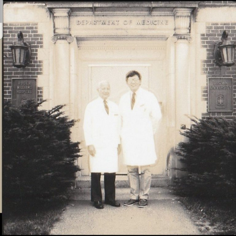 Paul Calabresi (left) with Ed Chu (right) in front of the Department of Medicine facade at Roger Williams Hospital which at the time was affiliated with Brown University.