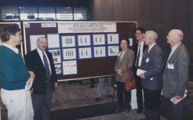 """Paul Calabresi (2nd from right) at his meeting poster on """"Predictive Sensitivity of Human Cancer Cells to Anticancer Agents In Vivo"""" with Mike Lipsky (2nd from left), Ming-Yu Chu (4th from right) and Lorrin Yee (3rd from right)."""